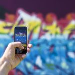 An iPhone user taking a photo of graffiti