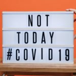 "A sign on a stool saying ""Not today, Covid-19"""